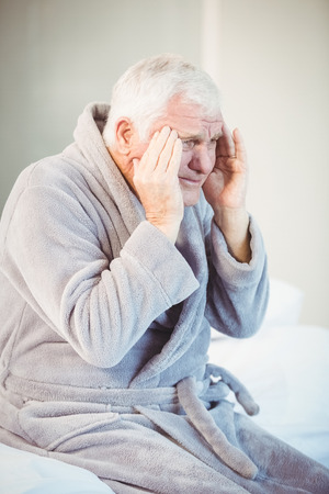 seniors suffering painful illness: Senior man suffering from headache while sitting on bed in room