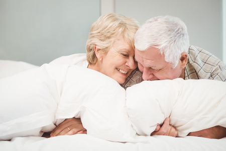 Happy playful senior couple resting in bed at home Foto de archivo