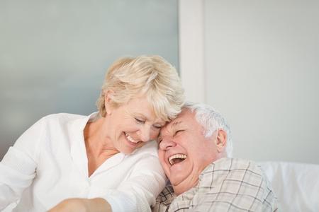 Šťastný starší pár směje v posteli doma Reklamní fotografie