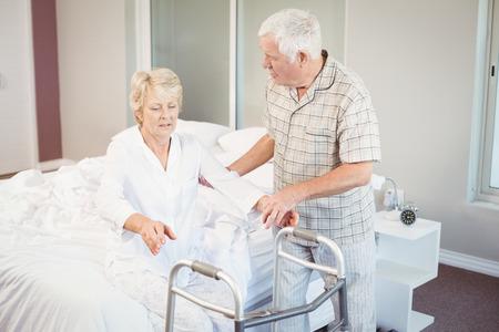levantandose: Hombre mayor que asiste a la mujer enferma en levantarse de la cama en la habitaci�n