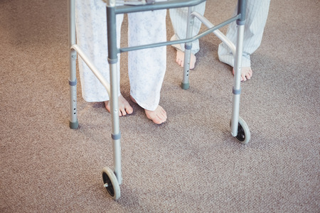 seniors suffering painful illness: Low section of elderly man and woman with walker on carpet in bedroom Stock Photo