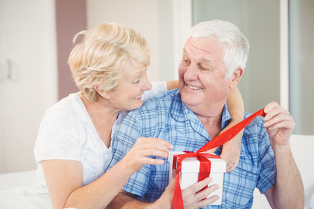opening gift: Happy senior couple opening gift in bedroom at home