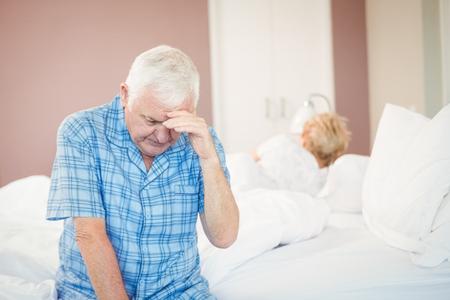 tensed: Tensed senior man in bedroom at home Stock Photo