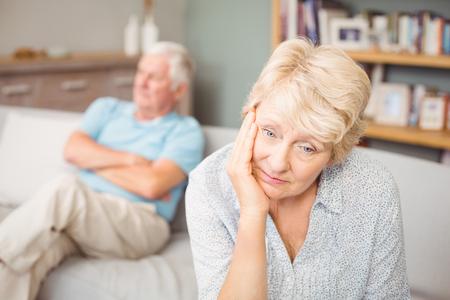 tensed: Tensed senior couple sitting on sofa at home