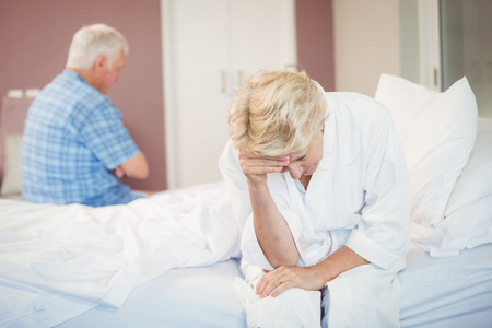 tensed: Tensed senior couple sitting in bedroom at home