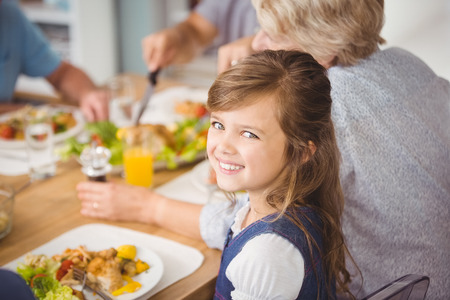 multi family house: Happy girl having breakfast with family at home