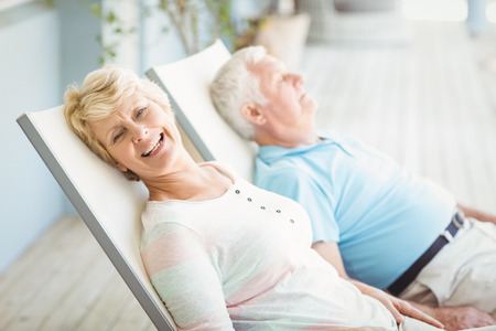 High angle view of senior couple relaxing on lounge chair at porch Stock Photo