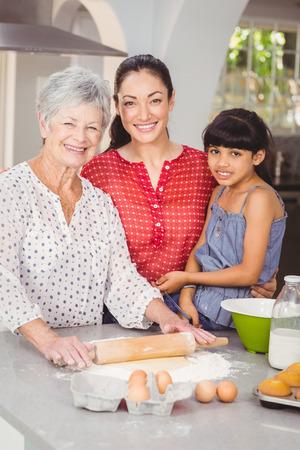 haciendo pan: Retrato de la abuela con la familia que hace el pan en la cocina