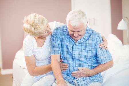 Wife comforting senior husband suffering from stomach pain at home