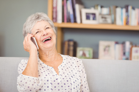 telephone call: Senior woman talking on mobile phone at home
