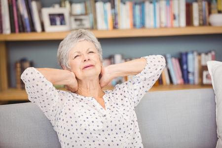seniors suffering painful illness: Senior woman suffering from neck pain on sofa