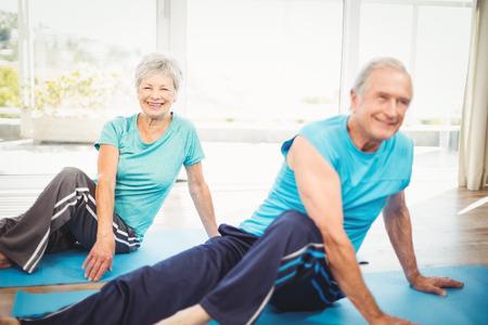 fitness hombres: Feliz altos pareja haciendo yoga en la estera de ejercicio en casa