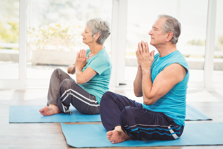 Senior couple performing yoga while sitting at home