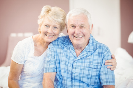 arm around: Portrait of smiling senior couple with arm around at home Stock Photo