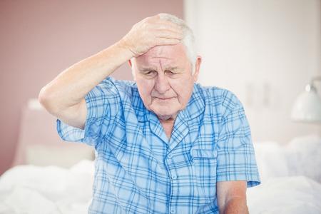 seniors suffering painful illness: Senior man suffering from headache at home Stock Photo