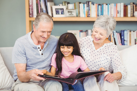 Grandparents showing album to granddaughter in living rooom at home