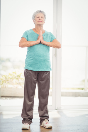 hands clasped: Senior woman with hands clasped performing yoga at home