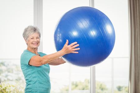 Porträt der glücklichen älteren Frau, die zu Hause blauen Übungsball hält Standard-Bild
