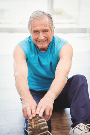 touching toes: Senior man touching toes while exercising at health club