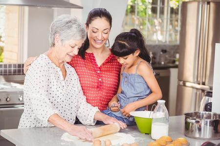 haciendo pan: Abuela con la familia que hace el pan en la cocina