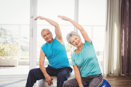 Portrait of happy senior couple performing exercise at home