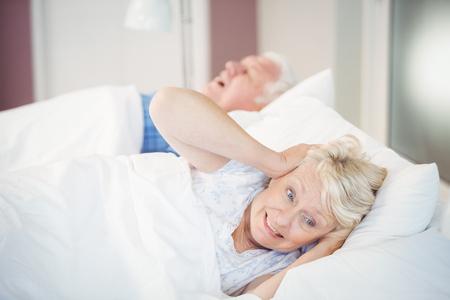 blocking: Irritated senior woman blocking ears while man snoring on bed