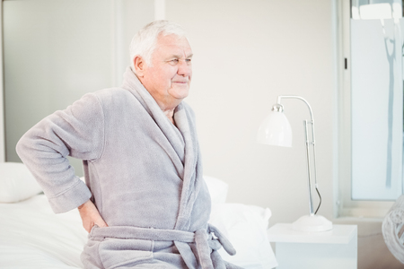 lower back pain: Upset senior man sitting with lower back pain on bed at home