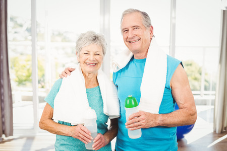 Portrait of happy senior couple holding bottle while exercising at home