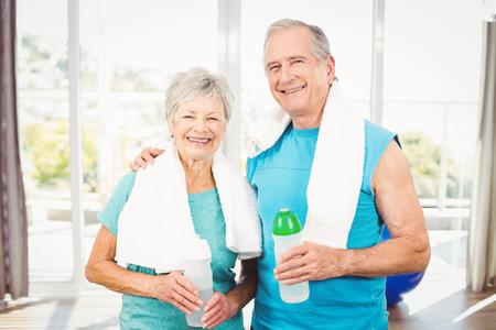Ritratto di felice coppia senior bottiglia di contenimento, mentre l'esercizio a casa Archivio Fotografico - 53959919