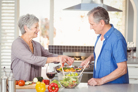 preparing food: Side view of happy senior couple preparing food while standing at kitchen counter