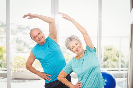 Portrait of smiling senior couple exercising at home Stock Photo