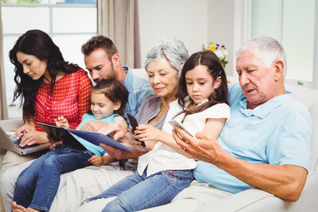 family sofa: Family using technologies while sitting on sofa at home
