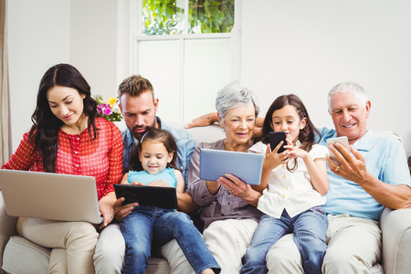 family sofa: Happy family using technologies while sitting on sofa at home