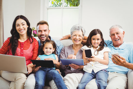 multi family house: Portrait of happy family holding technologies while sitting on couch at home
