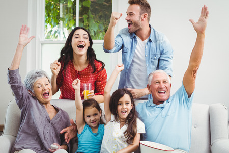 family sofa: Multi generation family on sofa cheering while watching television at home Stock Photo