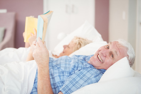 man holding book: Portrait of senior man holding book and lying on bed at home Stock Photo