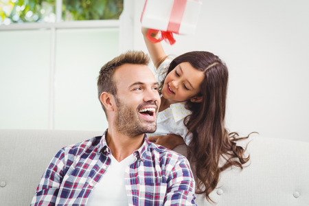 Happy daughter and father with gift at home Stock Photo