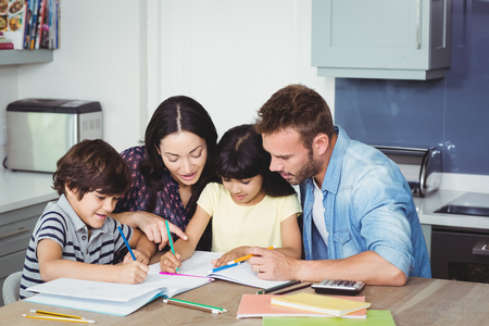 ni�os ayudando: Parents helping children in doing homework at home Foto de archivo