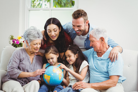 Happy family on sofa looking at terrestrial globe Imagens