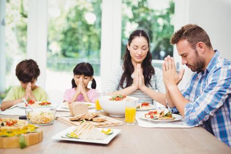 family praying: Familia que ruega mientras est� sentado en mesa de comedor en el hogar