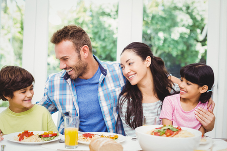 arm around: Smiling family with arm around while sitting at dining table with food in home Stock Photo
