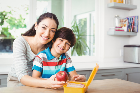 lunch table: Portrait of smiling mother and son with lunch box at table Stock Photo