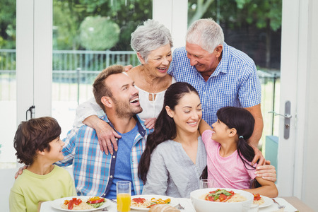 Smiling multi generation family at dining table in home