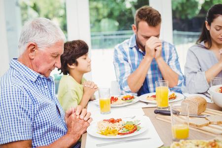 family praying: familia multi generaci�n de oraci�n, mientras sentado en la mesa de comedor en el hogar