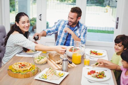 Familia feliz comiendo mientras estaba sentado en la mesa de comedor en casa