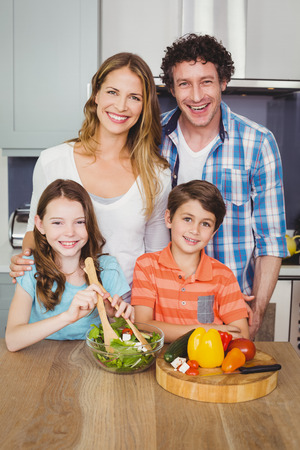 causal clothing: Portrait of happy family preparing vegetable salad in kitchen at home