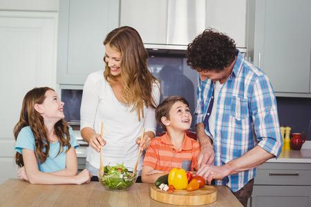 causal clothing: Smiling family preparing vegetable salad in kitchen