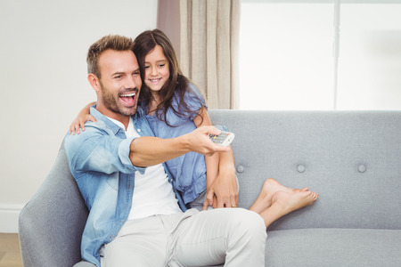 changing channel: Smiling daughter and father watching television at home