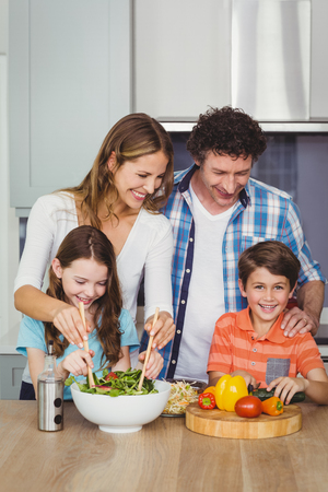 causal clothing: Happy family standing by table in kitchen at home Stock Photo