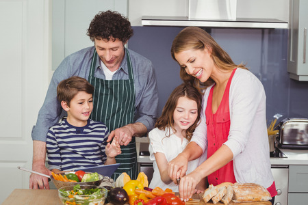 causal clothing: Happy parents standing with son and daughter in kitchen at home Stock Photo